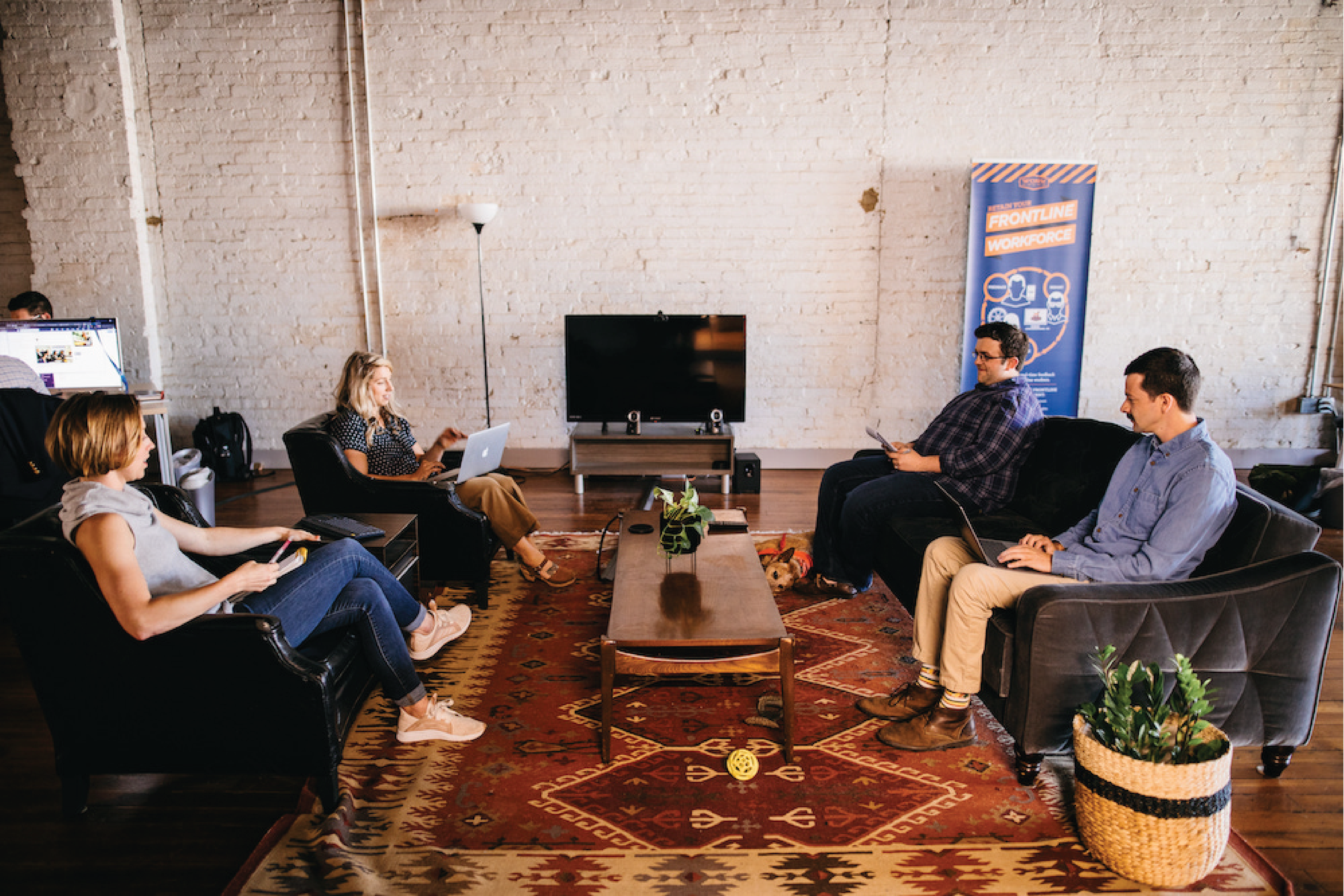 A picture of a group of people seated around a coffee table
