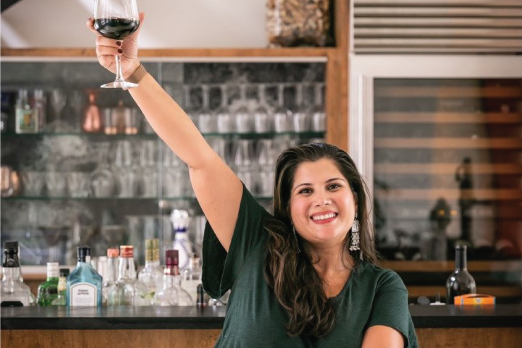 Spice Trail business owner Sujata Shahi Singh holds a glass of wine high in the air as she smiles standing in front of a bar