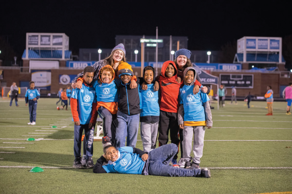 A photo shows seven kids and two coaches on a soccer filed posing.