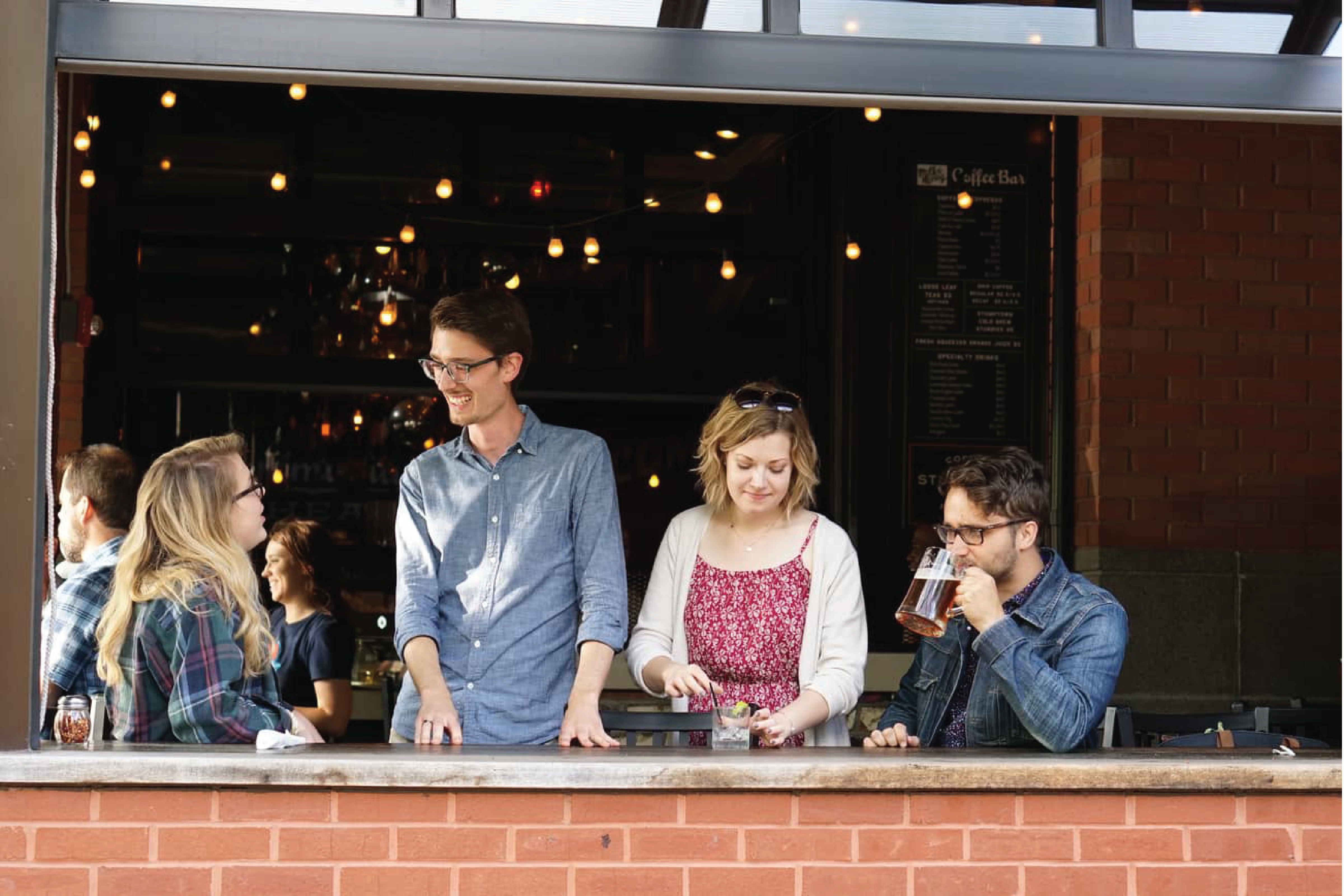 Pictured are four people networking and drinking beer at Oddstory