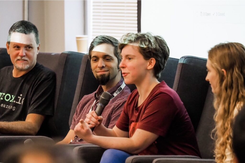 Pictured are two men and two women speaking on a panel