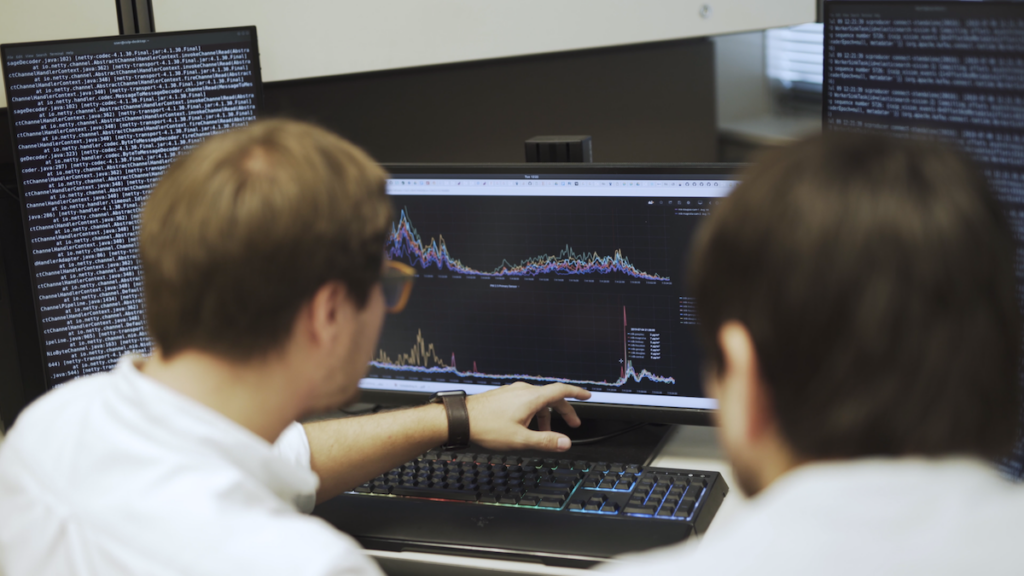 A picture of two data analysts looking at data on a computer screen