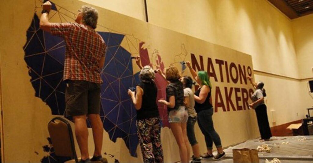 Pictured are a group of people writing on a wall with the words Nation Maker on it